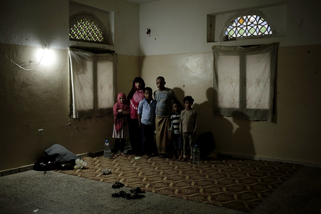 A family poses for a photograph in a shelter for displaced persons in Ibb, Yemen, in this Aug. 3, 2018, photo. This year the U.N., the U.S., Saudi Ara...