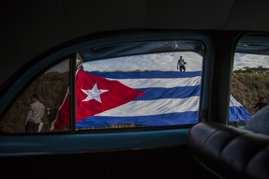 FILE - In this Dec. 2, 2016 file photo, a Cuban flag covers the side of the road where people wait for the funeral procession of Fidel Castro on the o...