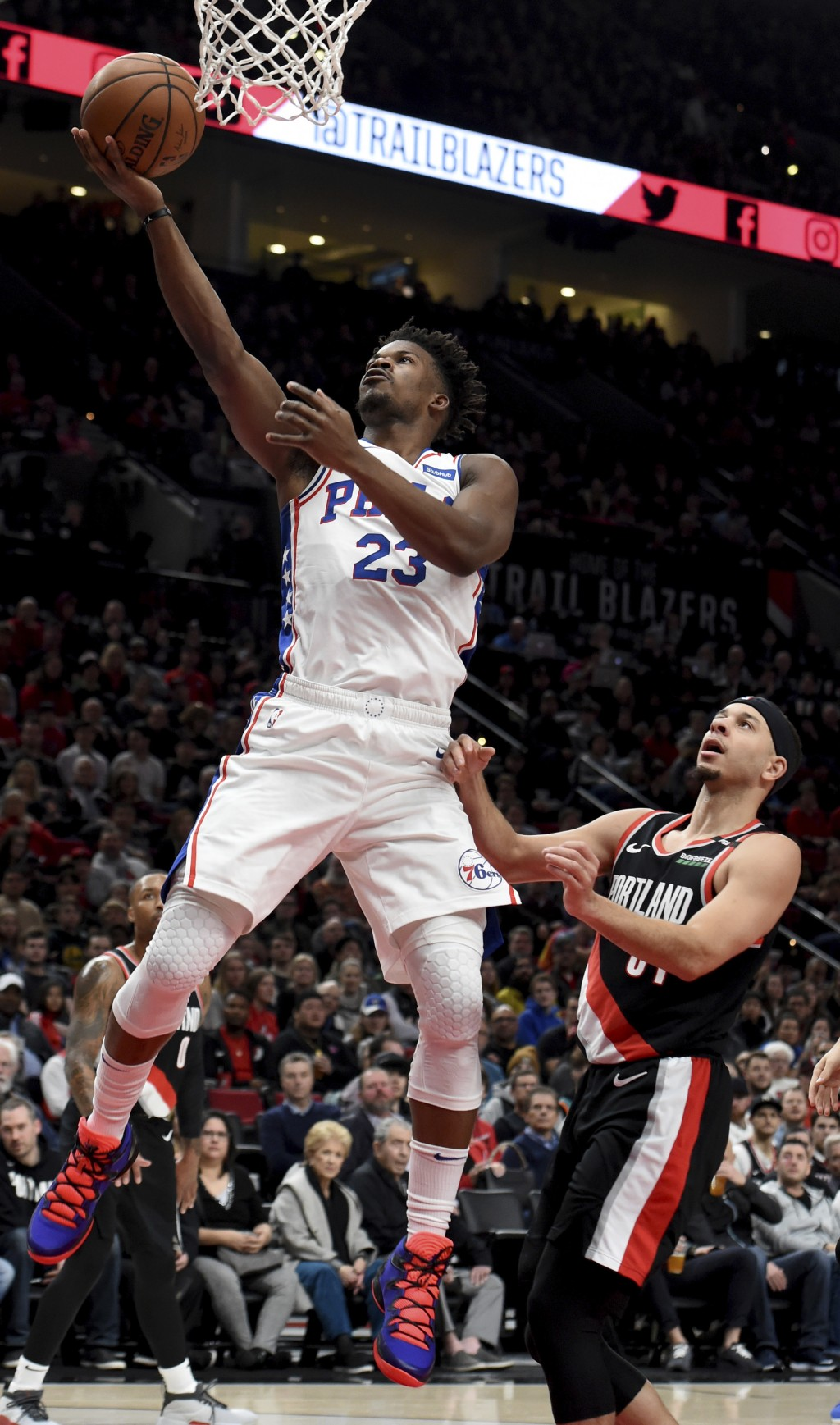 Philadelphia 76ers guard Jimmy Butler, left, drives to the basket on Portland Trail Blazers guard Seth Curry, right, during the first half of an NBA b...