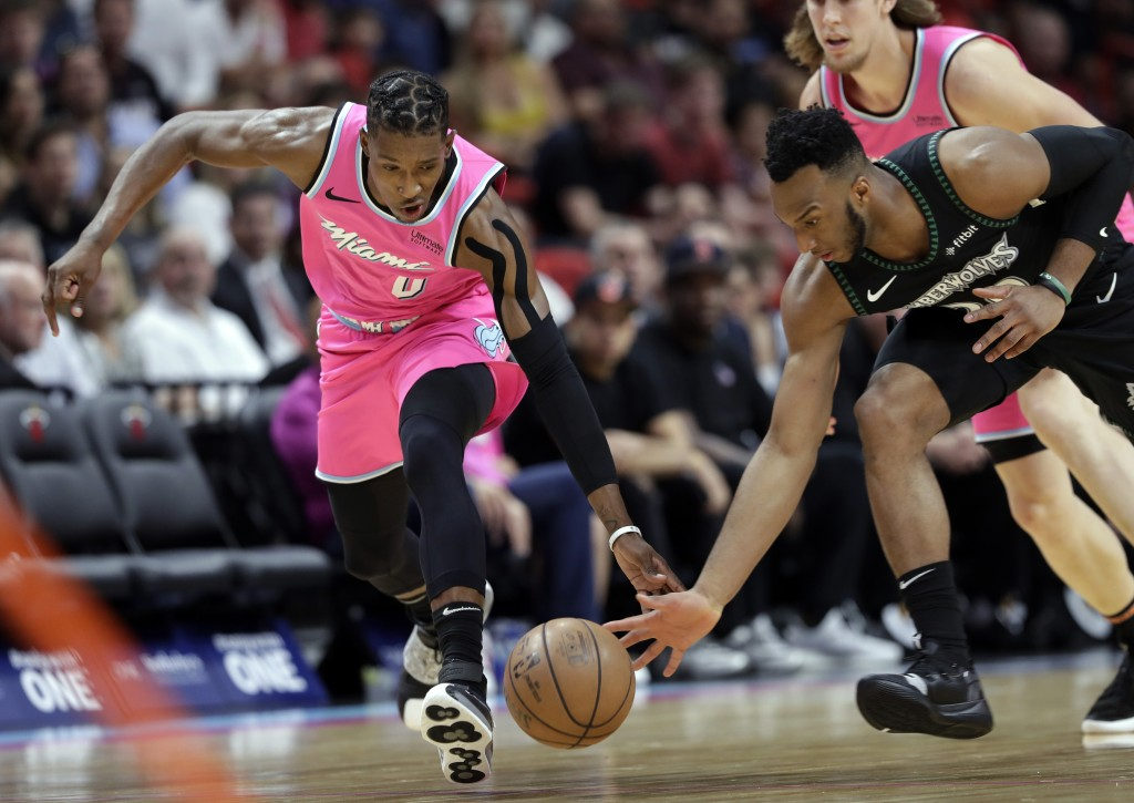 Miami Heat guard Josh Richardson (0) and Minnesota Timberwolves guard Josh Okogie go for a loose ball during the first half of an NBA basketball game,...