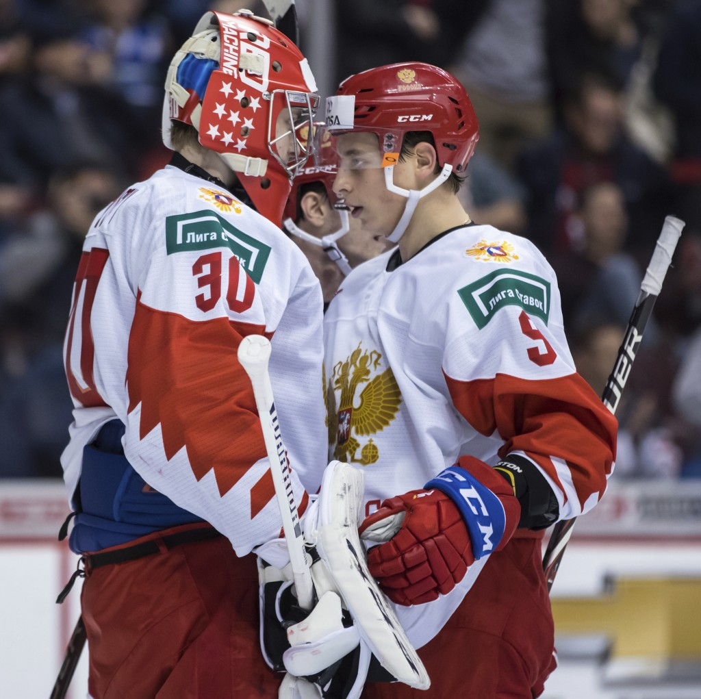 Russia goalie Danil Tarasov, left, and Artyom Galimov celebrate after Russia defeated Switzerland after a world junior hockey championships game in Va...