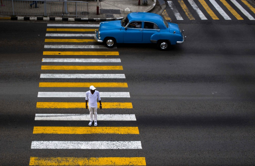 FILE - In this Nov. 16, 2018 file photo, a man uses the cross walk where the drivers passes in his classic car in Havana, Cuba. (AP Photo/Desmond Boyl...
