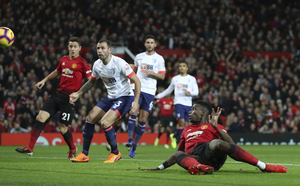 Manchester United's Paul Pogba, foreground, scores his side's first goal of the game against Bournemouth, during their English Premier League soccer m...