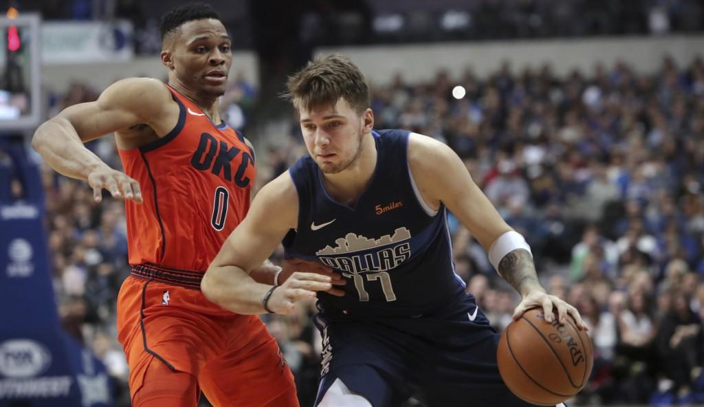 Dallas Mavericks forward Luka Doncic (77) drives past Oklahoma City Thunder guard Russell Westbrook (0) during the second half of an NBA basketball ga...