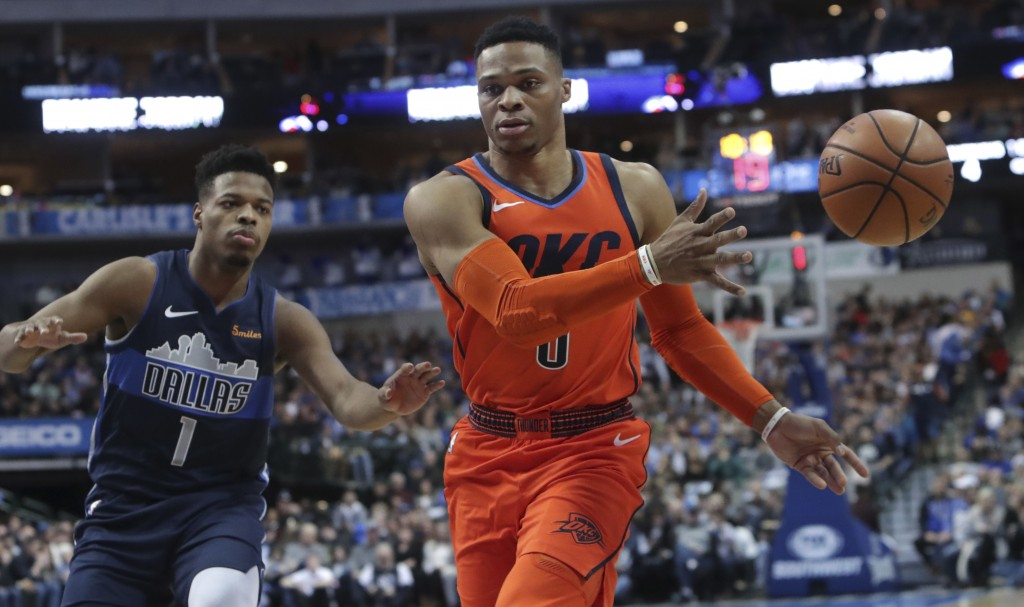 Oklahoma City Thunder guard Russell Westbrook (0) passes the ball in front of Dallas Mavericks guard Dennis Smith Jr. (1) during the first half of an ...