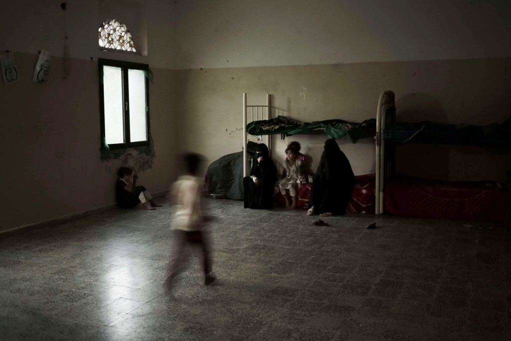 A family sits in their room at a shelter for displaced persons in Ibb, Yemen, in this Aug. 3, 2018, photo. Some observers have attributed the near-fam...