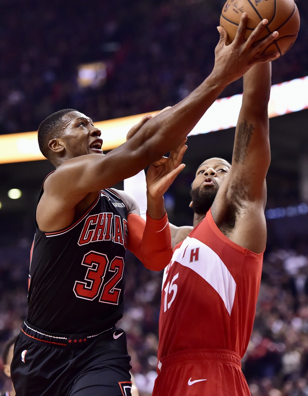 Chicago Bulls guard Kris Dunn (32) shoots as Toronto Raptors center Greg Monroe (15) defends during first-half NBA basketball game action in Toronto, ...