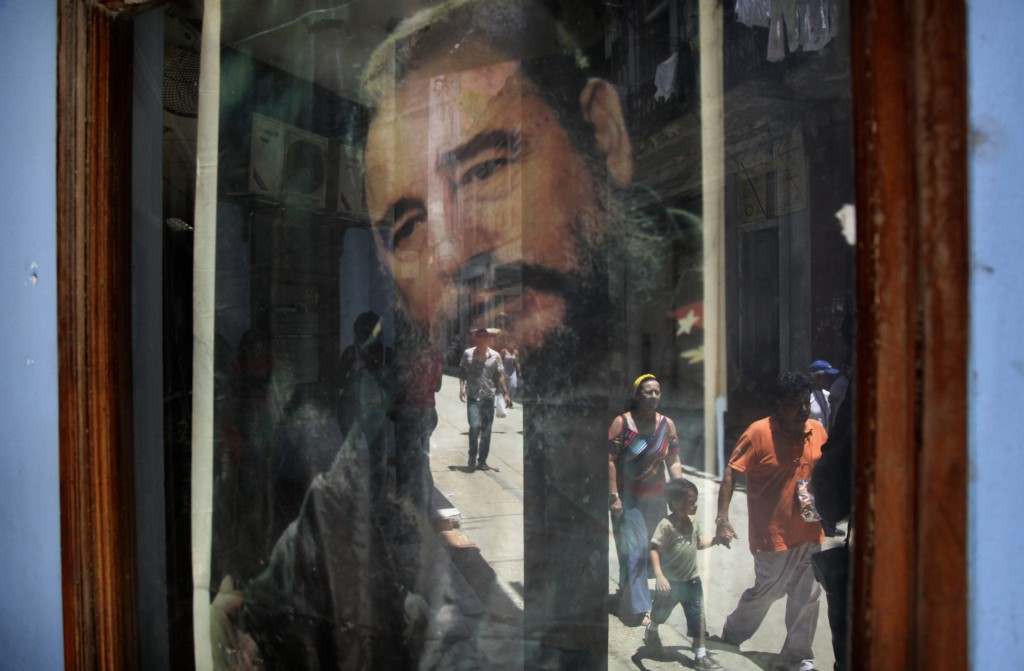 FILE - In this May 15, 2015 file photo, pedestrians are reflected in a post office window where a poster of Fidel Castro hangs in Havana, Cuba. (AP Ph...