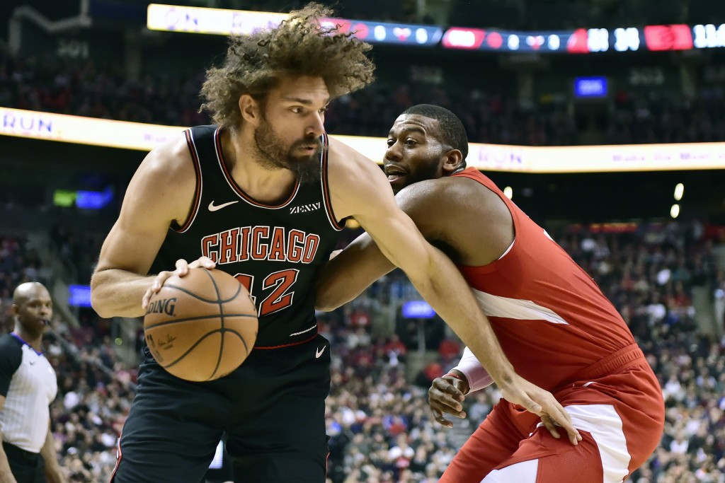 Chicago Bulls center Robin Lopez (42) drives to the net against Toronto Raptors center Greg Monroe (15) during the first half of an NBA basketball gam...
