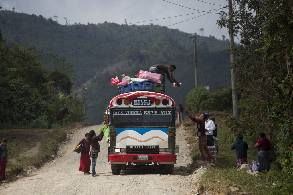 Passengers wait for their belongings to be taken off a bus at the entrance of Yalambojoch, Guatemala, Saturday, Dec. 29, 2018. Yalambojoch is an impov...