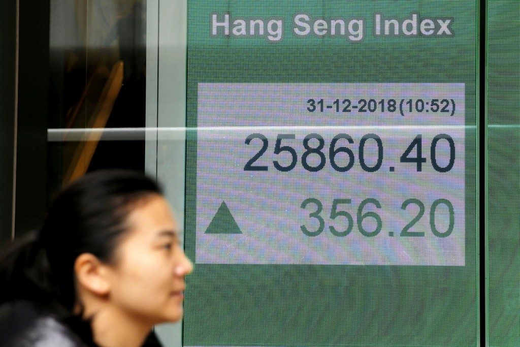 A woman passes an electronic board displaying the Hong Kong share index outside a bank in Hong Kong, Monday, Dec. 31, 2018. Shares are mostly higher i...