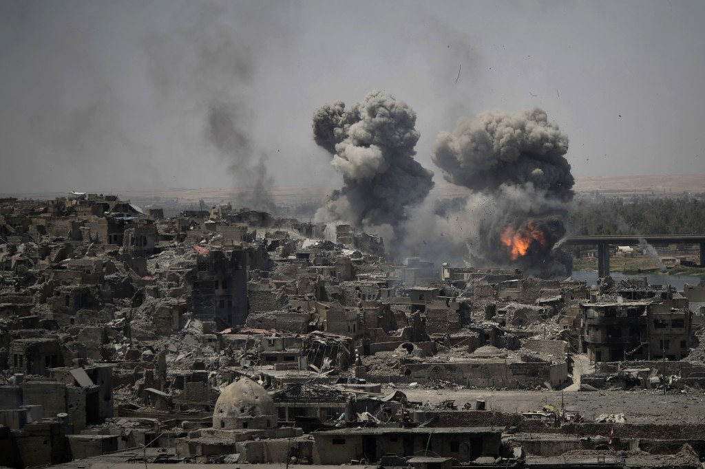 FILE - In this July 11, 2017 file photo, airstrikes target Islamic State group positions on the edge of the Old City, in Mosul, Iraq. The latest plung...