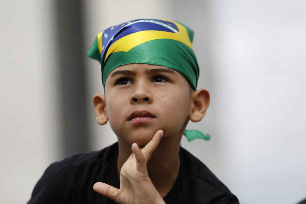 A child waits for the swearing-in ceremony of Brazil's new President Jair Bolsonaro, in front of the Planalto palace in Brasilia, Brazil, Tuesday Jan....