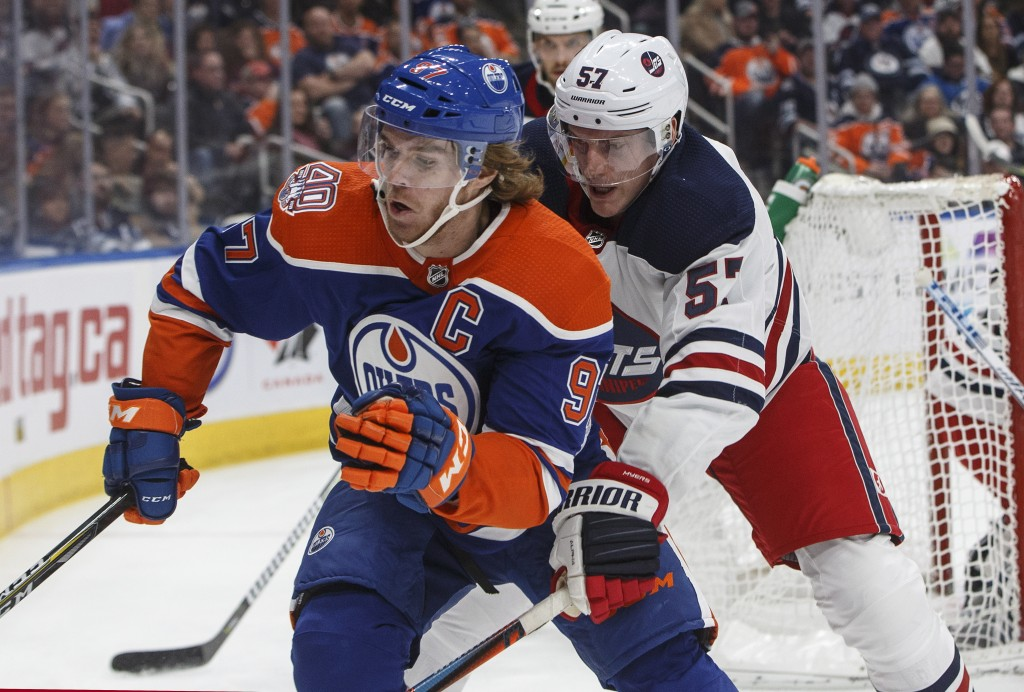 Winnipeg Jets' Tyler Myers (57) chases Edmonton Oilers' Connor McDavid (97) during second-period NHL hockey game action in Edmonton, Alberta, Monday,