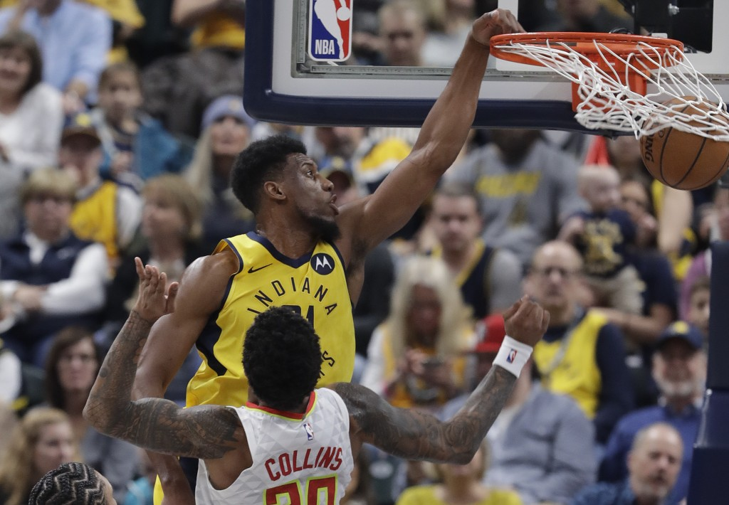 Indiana Pacers' Thaddeus Young (21) dunks against Atlanta Hawks' John Collins during the first half of an NBA basketball game, Monday, Dec. 31, 2018, ...