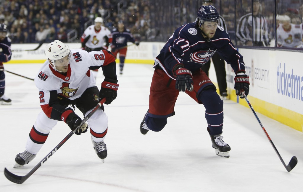 Ottawa Senators' Dylan DeMelo, left, and Columbus Blue Jackets' Josh Anderson chase the puck during the second period of an NHL hockey game Monday, De