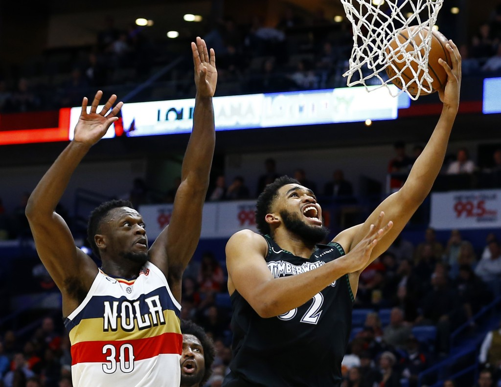 Minnesota Timberwolves center Karl-Anthony Towns (32) makes a basket as New Orleans Pelicans forward Julius Randle (30) tries to defend during the fir
