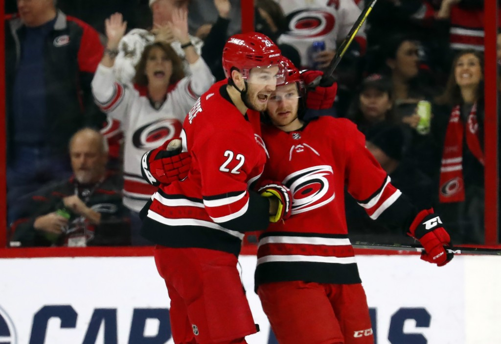 Carolina Hurricanes' Lucas Wallmark, right, is congratulated on his goal by teammate Brett Pesce (22) during the first period of an NHL hockey game ag
