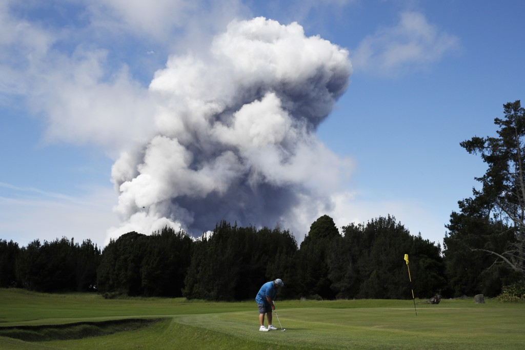 FILE - In this Monday, May 21, 2018 file photo,m Doug Ralston plays golf in Volcano, Hawaii, as a huge ash plume rises from the summit of Kiluaea volc