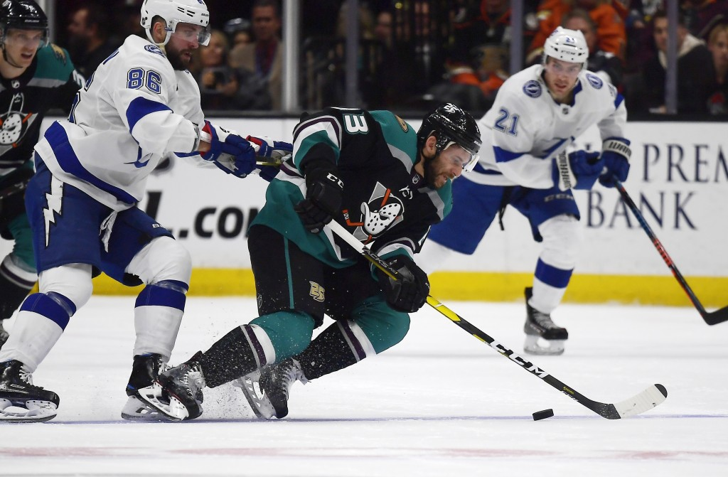 Anaheim Ducks center Brian Gibbons, center, falls as he takes the puck while under pressure from Tampa Bay Lightning right wing Nikita Kucherov, left,...