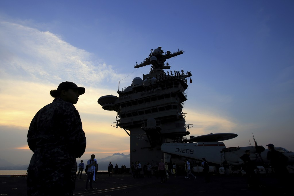 FILE - In this Monday, March 5, 2018 file photo, people stand on the deck of the USS Carl Vinson aircraft carrier as it docks in Danang bay, Vietnam.