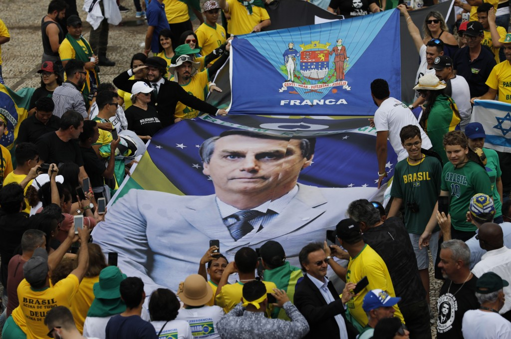People hold a banner with a photo of Brazil's former army captain Jair Bolsonaro before the swearing-in ceremony, in front of the Planalto palace in B