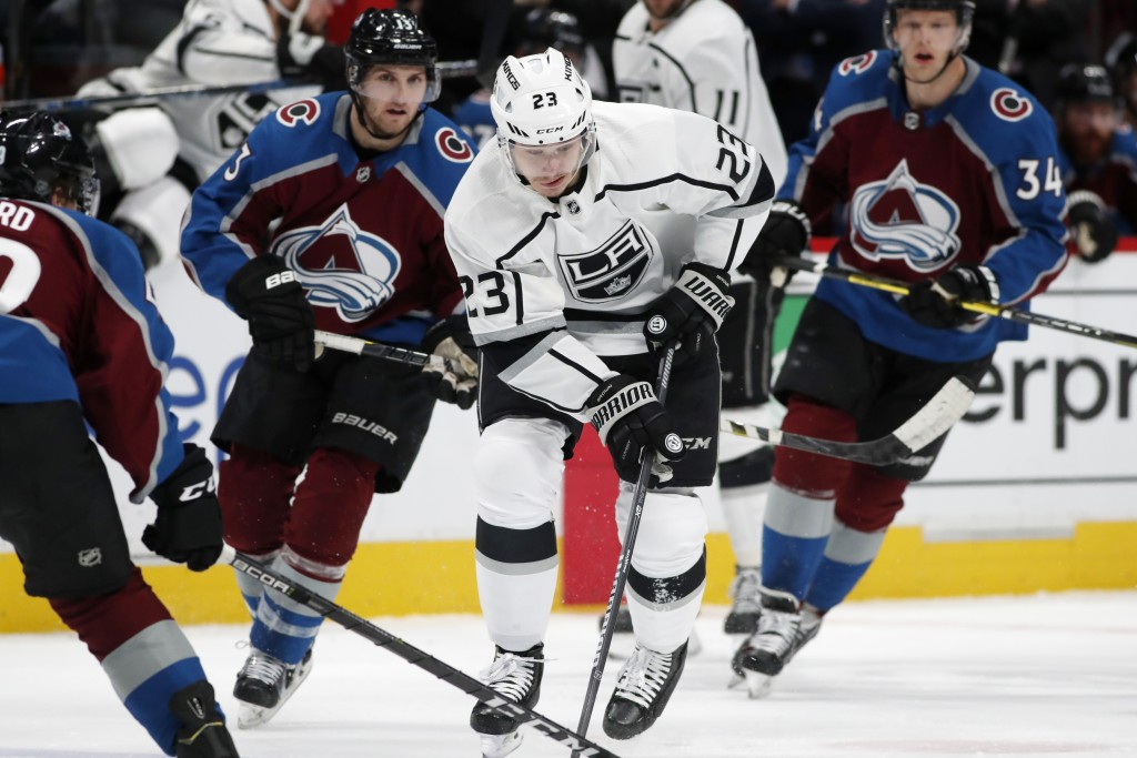 Los Angeles Kings right wing Dustin Brown (23) tries to maneuver the puck as, from left, Colorado Avalanche defenseman Samuel Girard and centers Alexa...