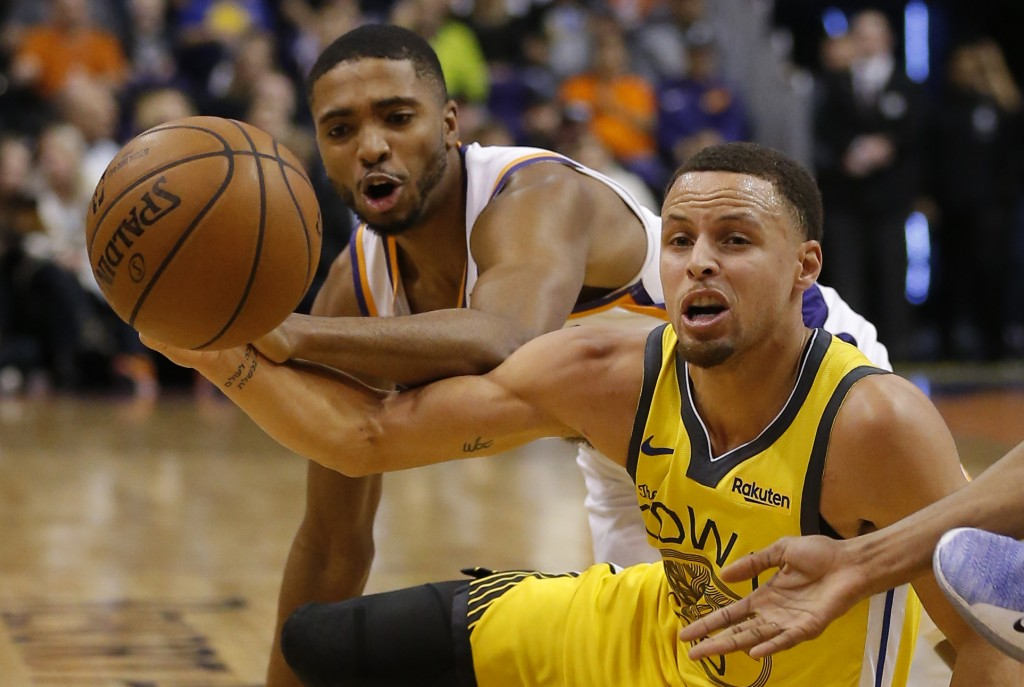 Golden State Warriors guard Stephen Curry, right, and Phoenix Suns forward Mikal Bridges vie for the ball during the first half of an NBA basketball g...