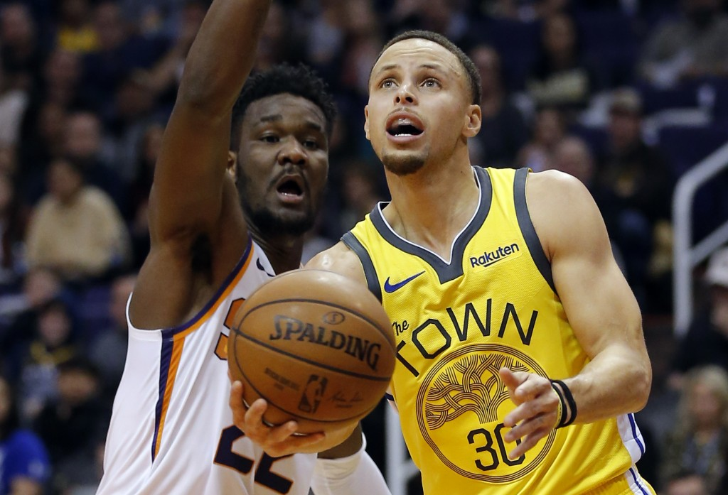 Golden State Warriors guard Stephen Curry (30) drives past Phoenix Suns center Deandre Ayton during the first half of an NBA basketball game Monday, D...