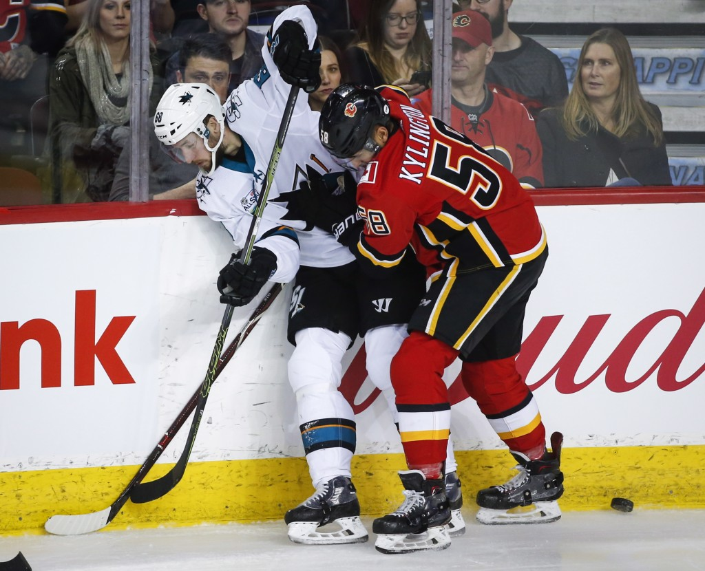 San Jose Sharks' Melker Karlsson, left, of Sweden, and Calgary Flames' Oliver Kylington, of Sweden, compete for the puck during the first period of an