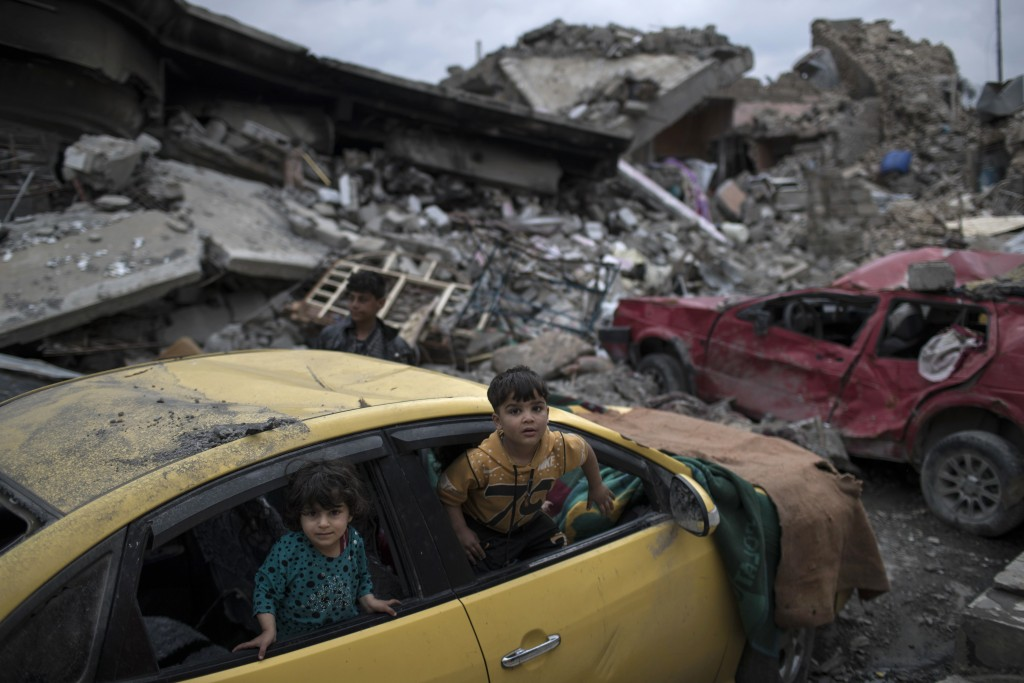 FILE - In this April 1, 2017 file photo, children play inside a damaged car, amid heavy destruction in a neighborhood recently retaken by Iraqi securi