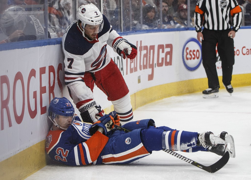 Winnipeg Jets' Ben Chiarot (7) checks Edmonton Oilers' Tobias Rieder (22) during second-period NHL hockey game action in Edmonton, Alberta, Monday, De...