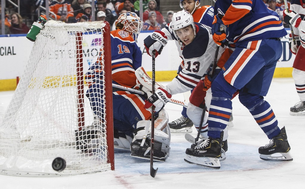Winnipeg Jets' Brandon Tanev (13) is stopped by Edmonton Oilers' goalie Mikko Koskinen (19) during first-period NHL hockey game action in Edmonton, Al...