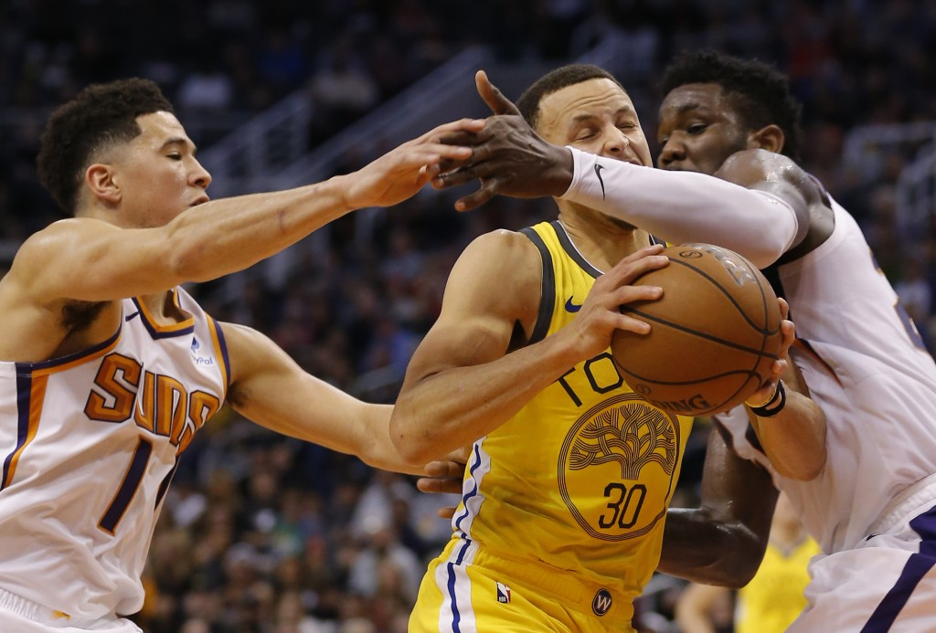 Golden State Warriors guard Stephen Curry (30) drives between Phoenix Suns' Devin Booker (1) and Deandre Ayton during the first half of an NBA basketb...