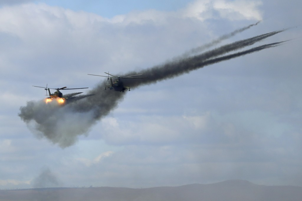FILE - In this Thursday, Sept. 13, 2018 file photo, military helicopters fire weapons about 250 kilometers (156 miles) north of the city of Chita duri