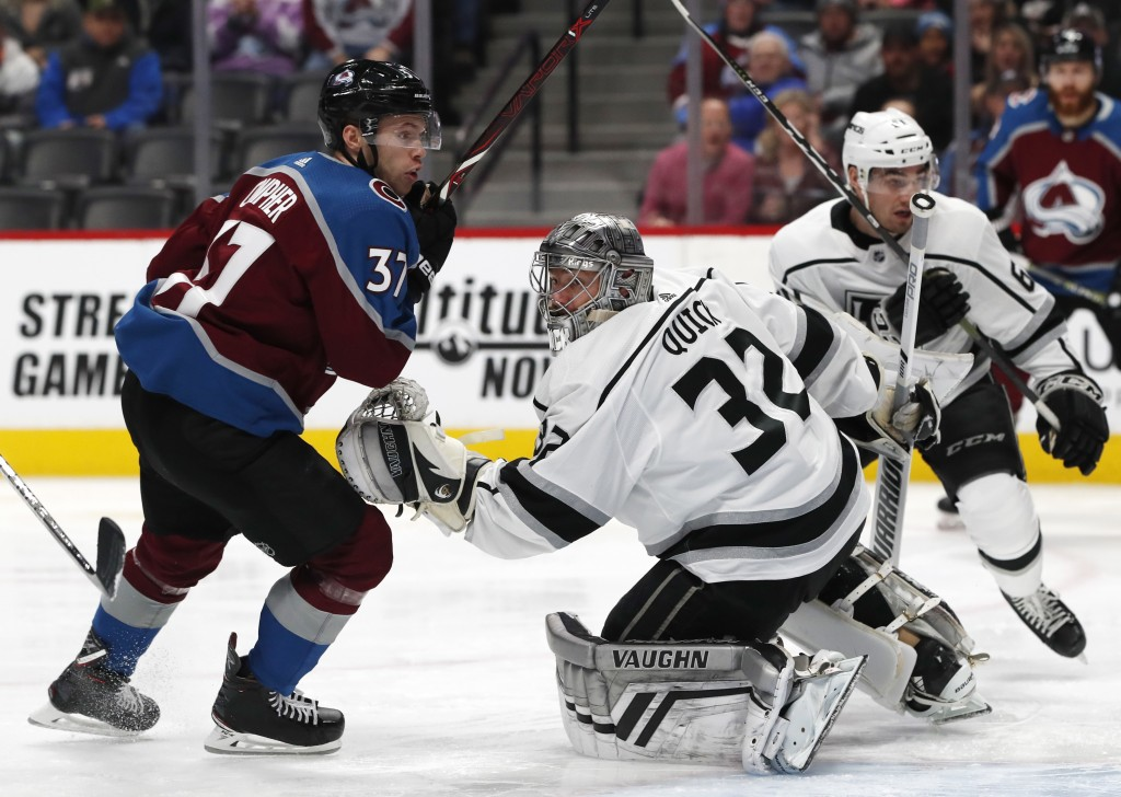 Colorado Avalanche left wing J.T. Compher watches the puck as Los Angeles Kings goaltender Jonathan Quick tries to make a glove save of a shot as defe...