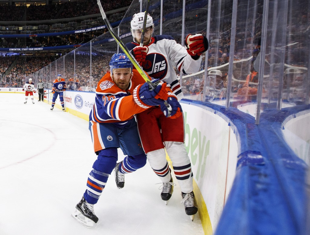 Winnipeg Jets' Adam Lowry (17) and Edmonton Oilers' Kyle Brodziak (28) battle for the puck during first-period NHL hockey game action in Edmonton, Alb...