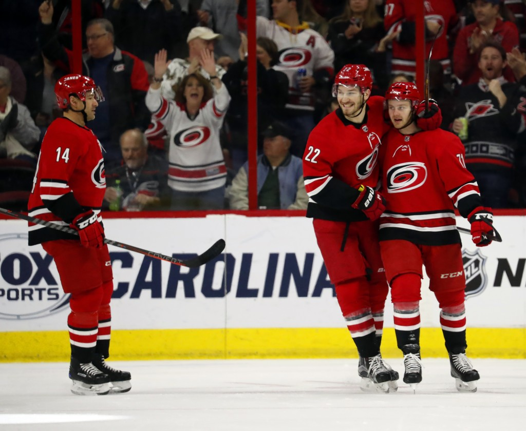 Carolina Hurricanes' Lucas Wallmark (71), right, is congratulated by teammates Brett Pesce (22) and Justin Williams (14) during the first period of an...