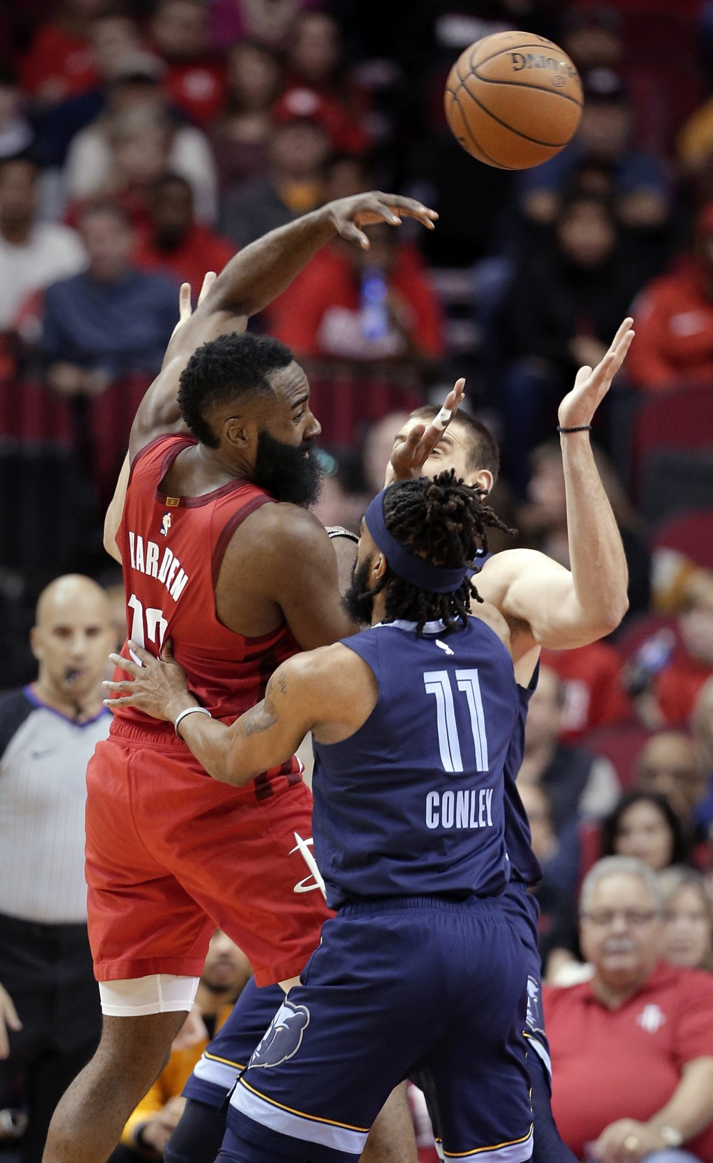 Houston Rockets guard James Harden (13) passes the ball over Memphis Grizzlies guard Mike Conley (11) and center Marc Gasol, back, during the first ha...