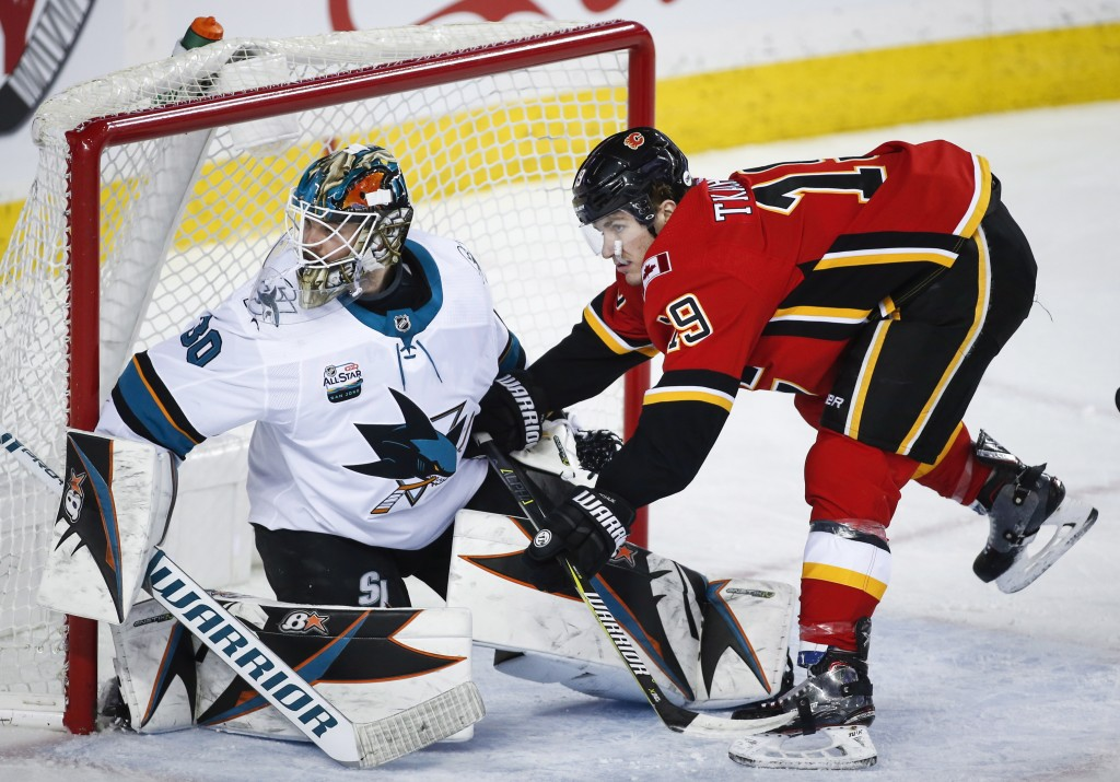 San Jose Sharks goalie Aaron Dell, left, guards the net as Calgary Flames' Matthew Tkachuk runs into him during the first period of an NHL hockey game