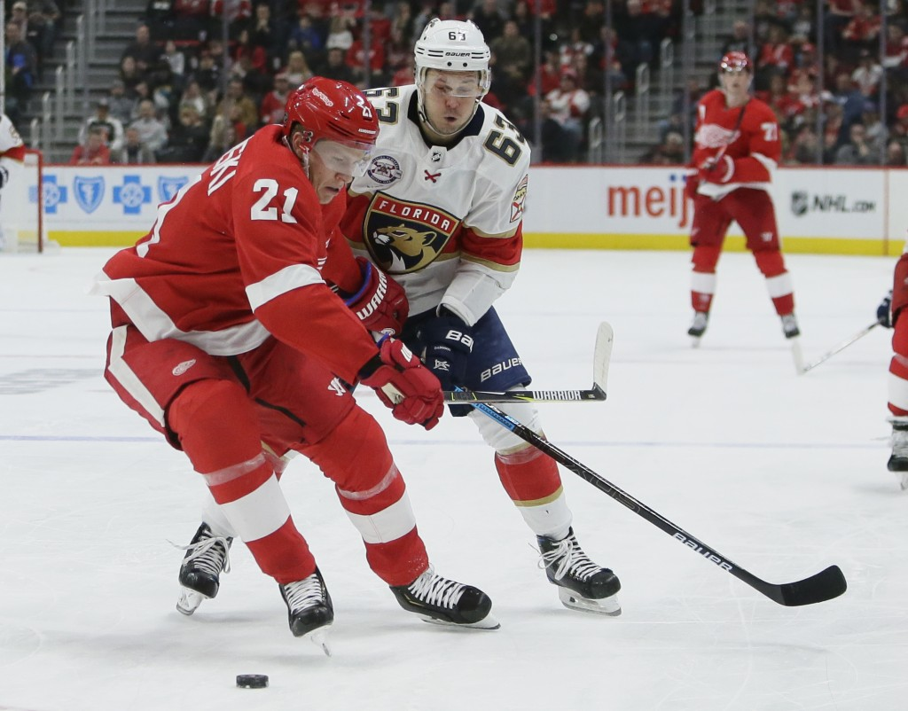Detroit Red Wings defenseman Dennis Cholowski (21) tries to keep Florida Panthers right wing Evgenii Dadonov (63), of Russia, from getting to the puck