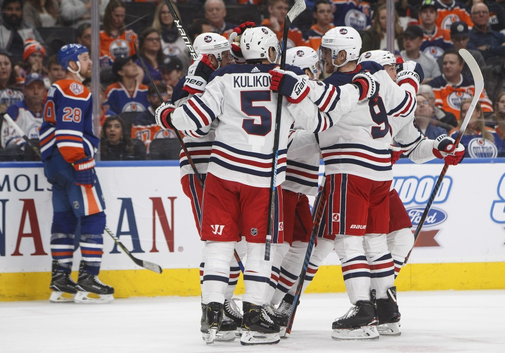 Winnipeg Jets celebrate a goal as Edmonton Oilers' Kyle Brodziak (28) skates past during the third period of an NHL hockey game Monday, Dec. 31, 2018,...
