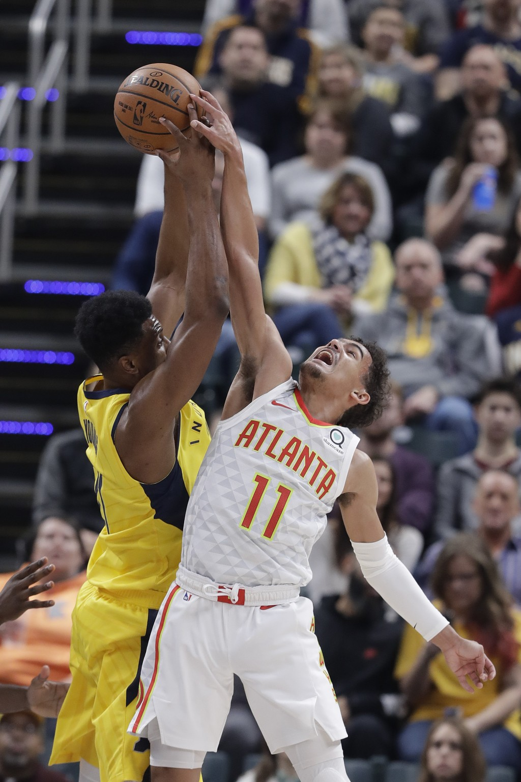 Indiana Pacers' Thaddeus Young, left, and Atlanta Hawks' Trae Young (11) battle for a rebound during the first half of an NBA basketball game, Monday,