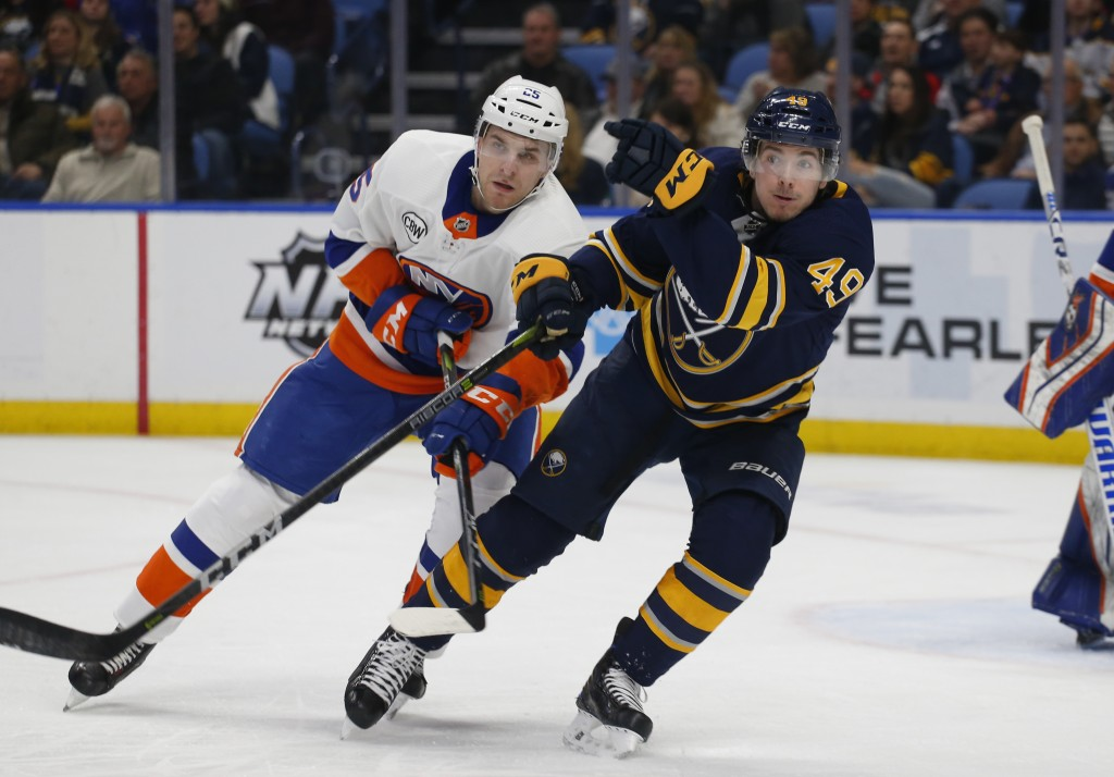 Buffalo Sabres forward C.J. Smith (49) and New York Islanders defenseman Devon Toews (25) battle for position during the first period of an NHL hockey...