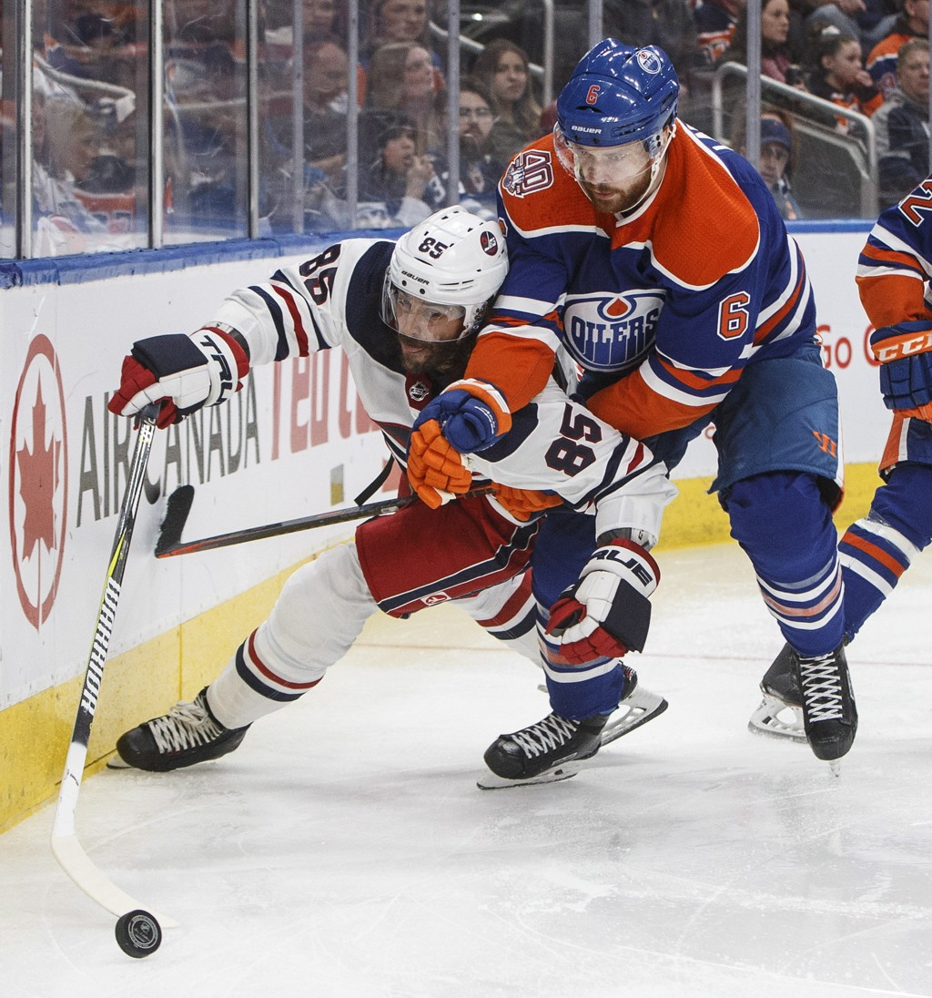 Winnipeg Jets' Mathieu Perreault (85) and Edmonton Oilers' Adam Larsson (6) battle for the puck during the third period of an NHL hockey game Monday, ...