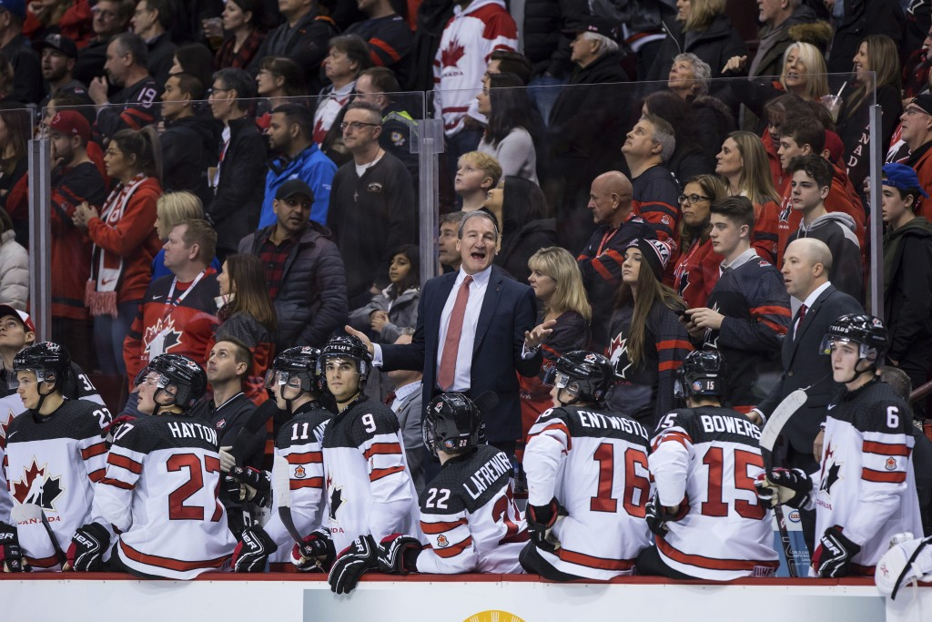 Canada head coach Tim Hunter, center, stands on the bench during third-period IIHF world junior hockey championship game action against Russia in Vanc