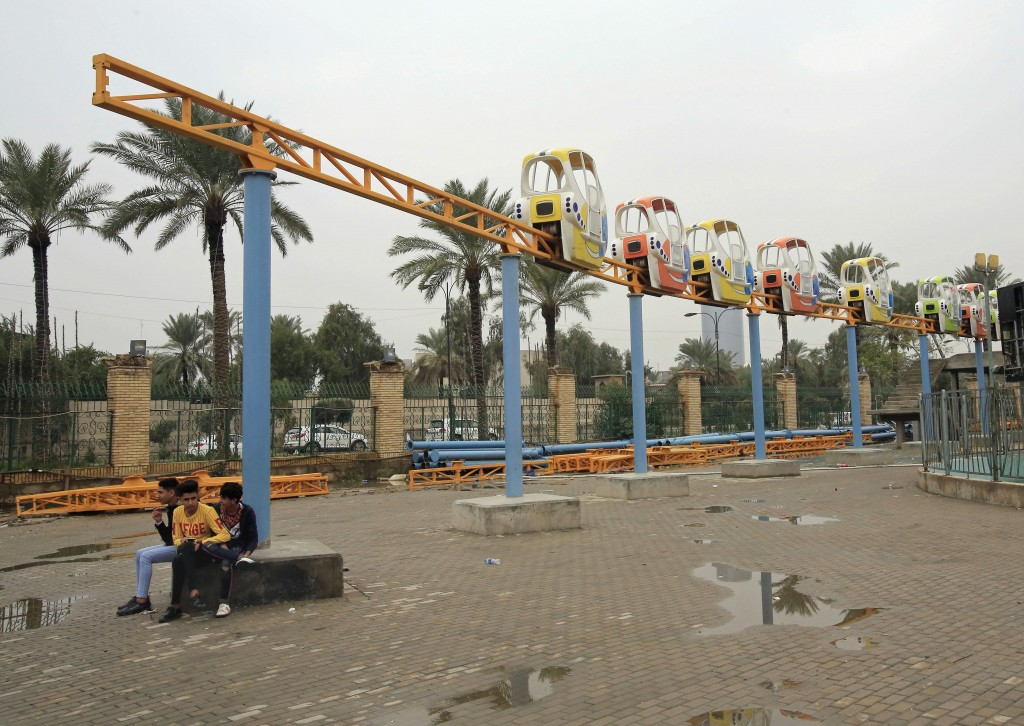 In this Dec. 18, 2018 photo, children sit beneath a roller coaster that is under construction at an amusement park in Baghdad, Iraq. The latest plunge