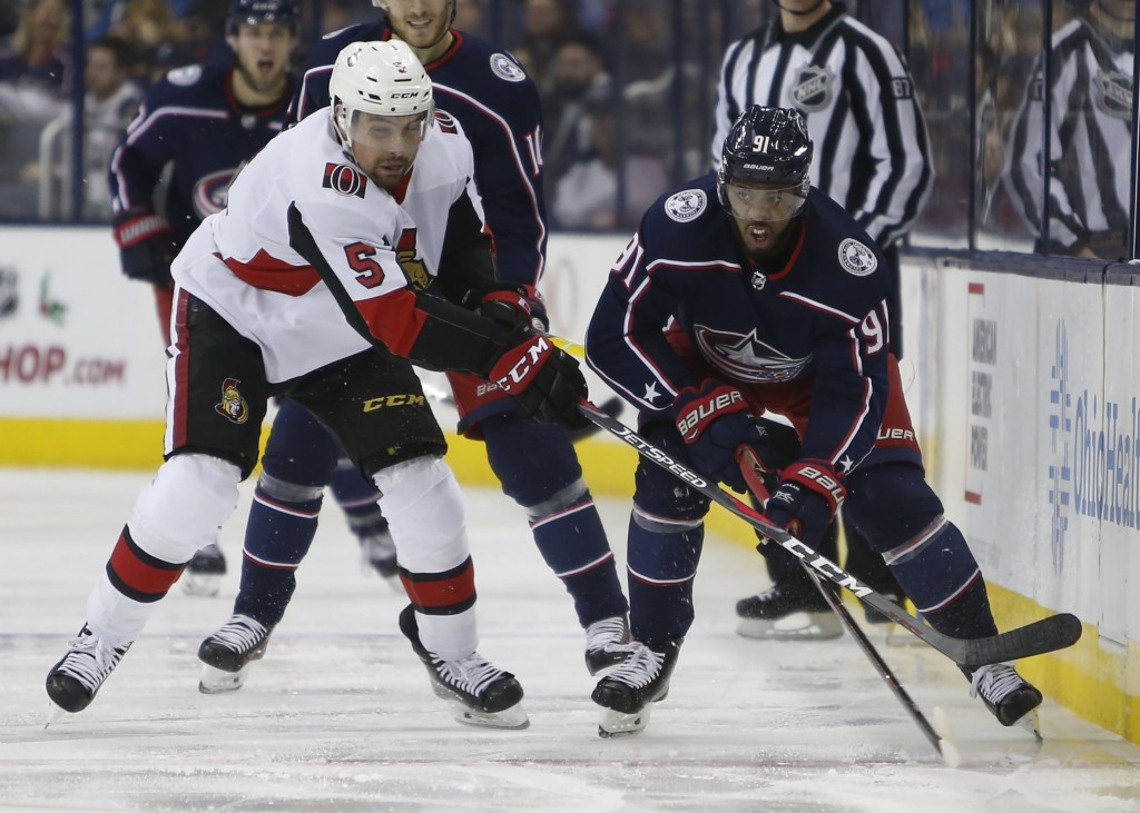 Ottawa Senators' Cody Ceci, left, and Columbus Blue Jackets' Anthony Duclair chase the puck during the second period of an NHL hockey game Monday, Dec...