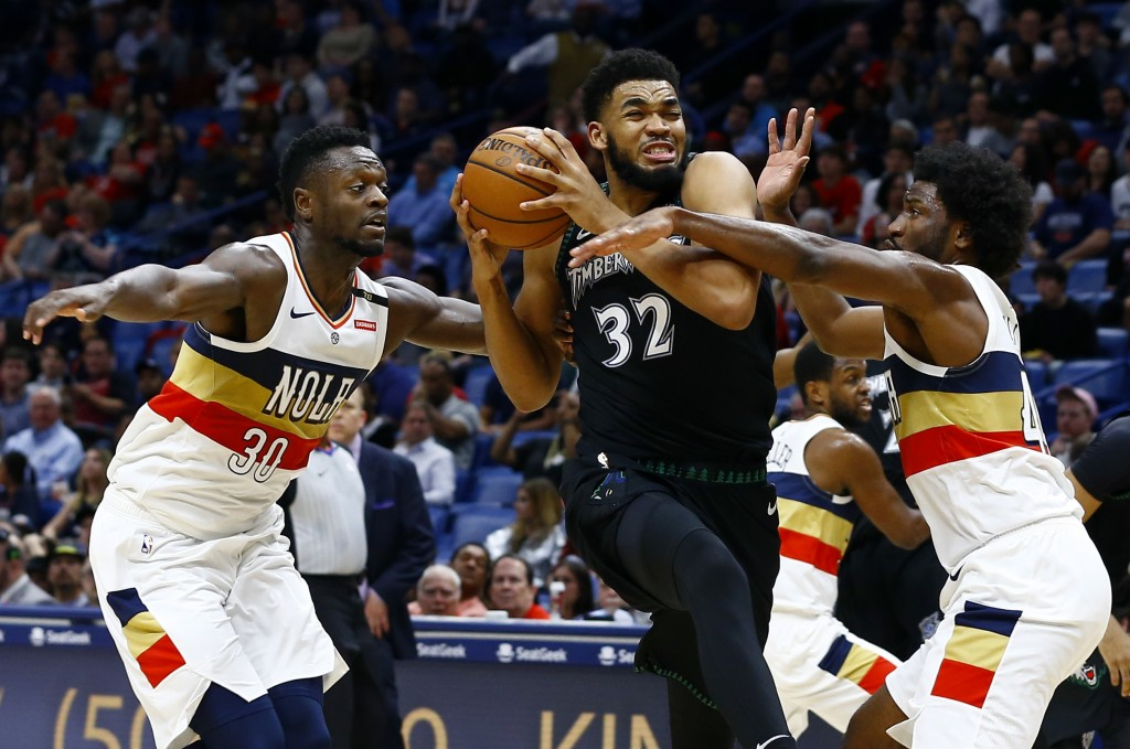 Minnesota Timberwolves center Karl-Anthony Towns (32) drives to the basket as New Orleans Pelicans forwards Julius Randle (30) and Solomon Hill (44) d