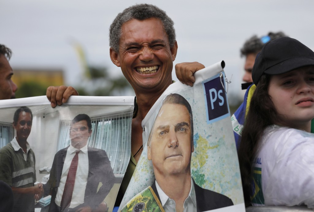 A supporter holds a photo of Brazil's former army captain Jair Bolsonaro before the swearing-in ceremony in front of the Planalto palace in Brasilia, ...